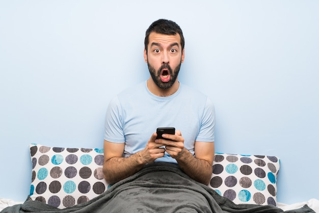 Man in bed surprised and sending a message
