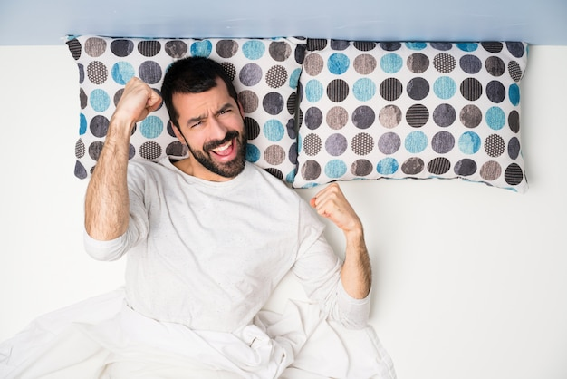 Man in bed in top view celebrating a victory