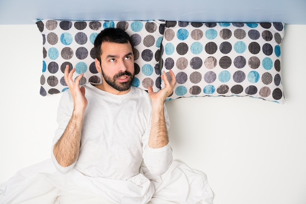 Man in bed in top view frustrated by a bad situation