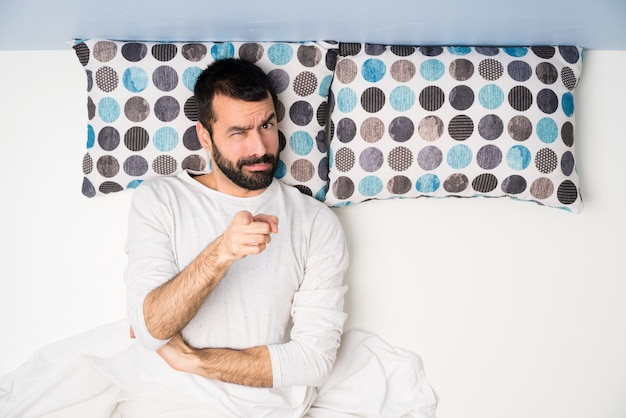 Man in bed in top view frustrated and pointing to the front