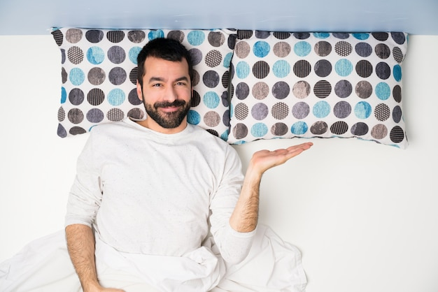 Man in bed in top view holding copyspace imaginary on the palm to insert an ad