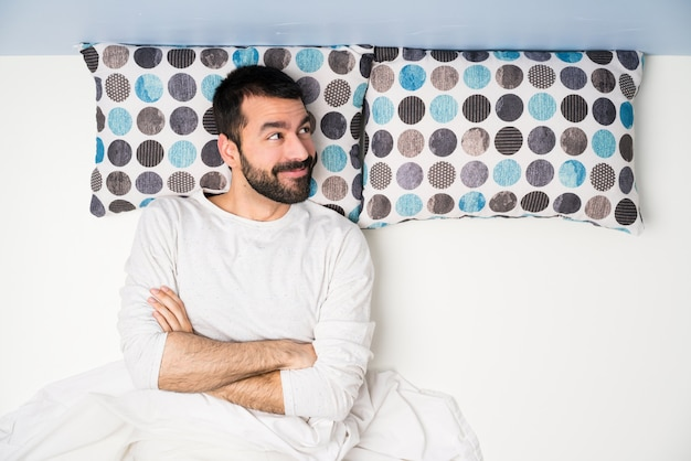Man in bed in top view looking up while smiling
