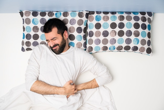 Man in bed in top view suffering from backache for having made an effort