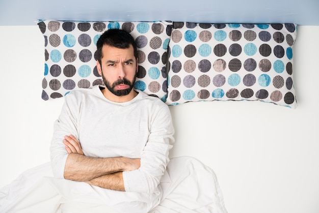 Man in bed in top view with sad and depressed expression