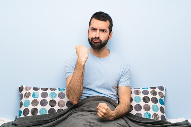 Man in bed with angry gesture