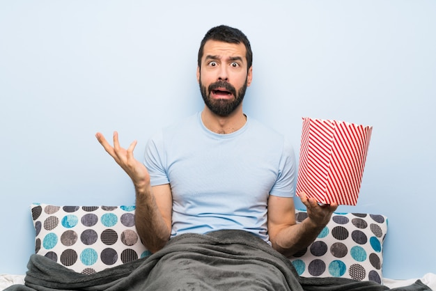 Man in bed with beard eating popcorns