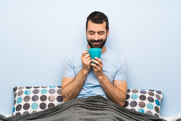 Man in bed with beard holding a cup of coffee