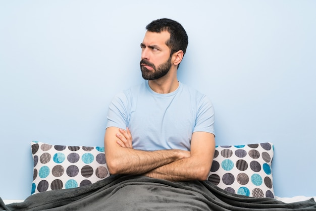 Man in bed with confuse face expression