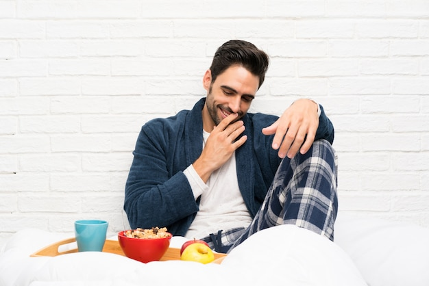 Man in bed with dressing gown and having breakfast smiling a lot
