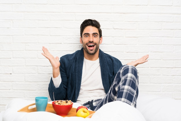 Man in bed with dressing gown and having breakfast with shocked facial expression