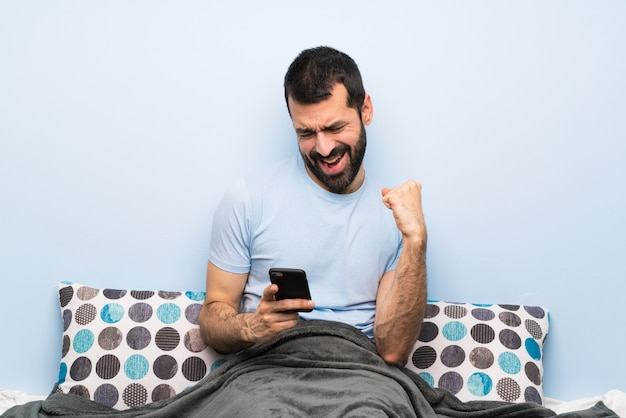 Man in bed with phone in victory position