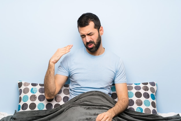 Man in bed with tired and sick expression