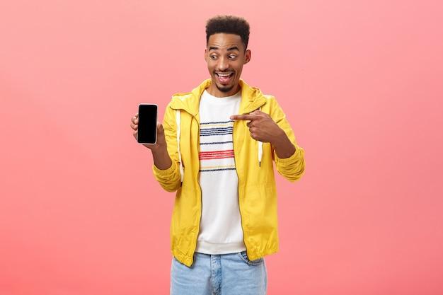 クールな新しい携帯電話に驚かされている男は、ピンクの背景の上にポーズをとって興奮して感動した顔でガジェット画面を指しているスマートフォンを保持しているデバイスの購入から幸せを隠すことはできません