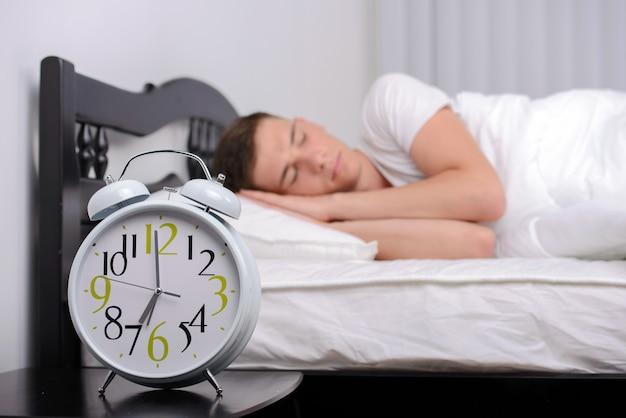 Man being awakened by an alarm clock in his bedroom