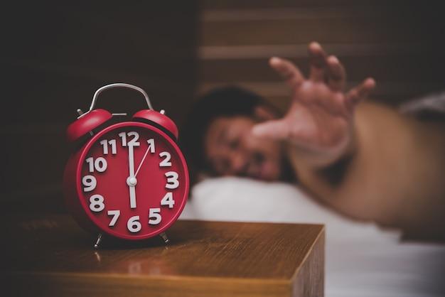 그의 침실에서 알람 시계에 의해 깨어 난 남자.