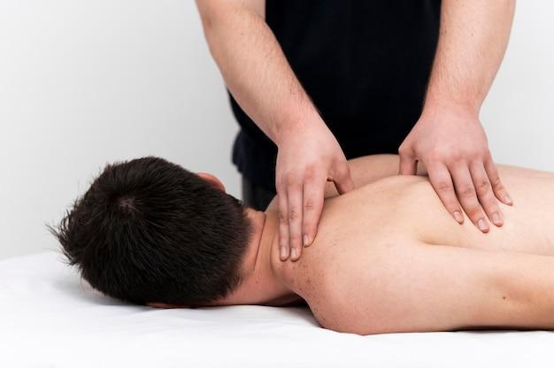 Физиотерапевт делает массаж спины мужчине
