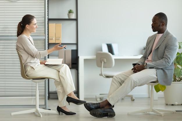 Мужчина дает интервью в помещении журналистом