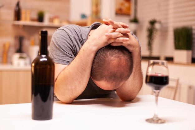 孤独で必死になってアルコール依存症の男性。アルコール依存症の問題で疲れ果てた不幸な人の病気と不安感。