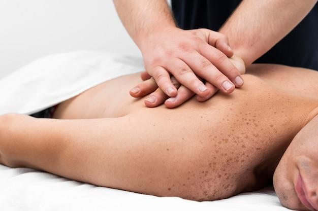 L'uomo viene massaggiato dal fisioterapista