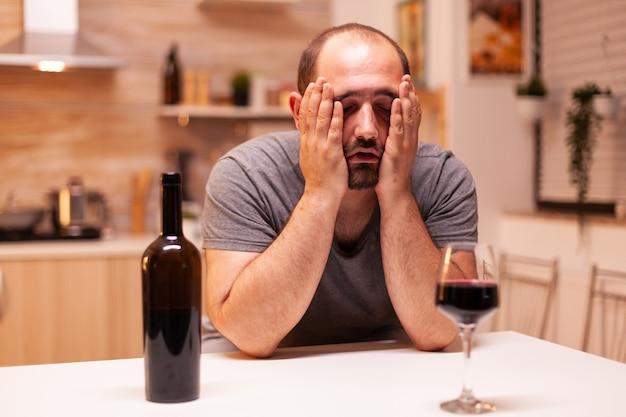 家で赤ワインのボトルの後に悲しくて二日酔いの男。アルコール依存症の問題で疲れ果てた不幸な人の病気と不安感。