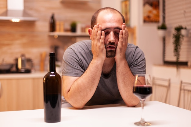 Man being sad and hangover after a bottle of red wine in home. unhappy person disease and anxiety feeling exhausted with having alcoholism problems.