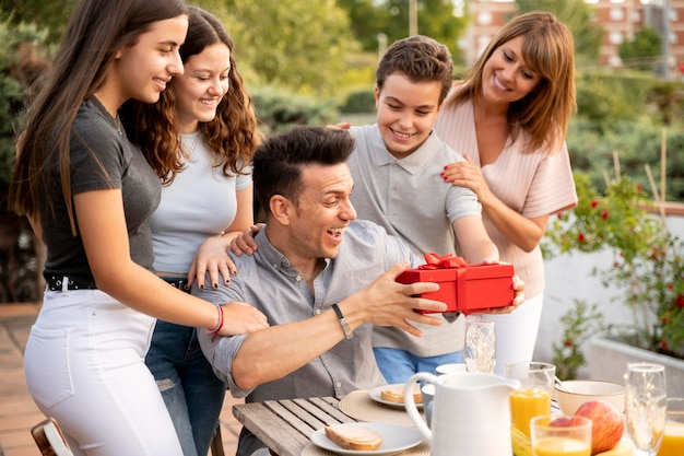 Man being surprised with gift at family gathering