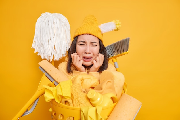 Man being tired of tidying up house surrounded by cleaning equipment laundry basket leans face on hands has displeased face expression wears hat isolated on yellow