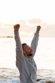 海の隣で勝利している男