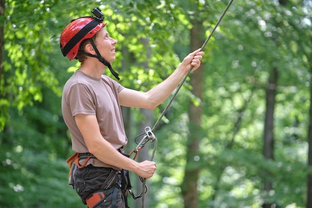 男はビレイ装置とロープでパートナークライマーをビレイします。ロック登山のセキュリティのための機器を保持しているクライマーの職人。