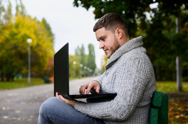 Man on a bench in the park with his laptop