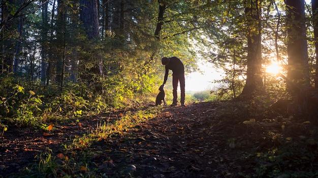 숲 속의 숲 사이에서 아름다운 자연을 즐기며 검은 개를 쓰다듬 기 위해 몸을 굽힌 남자