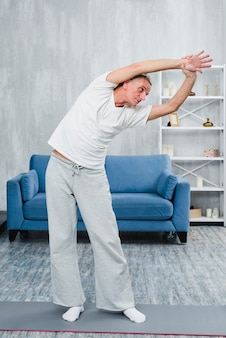Man bending while doing yoga in room