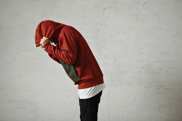 A man bends down and covers his head with the hood of his red parka, portrait from the side, on white