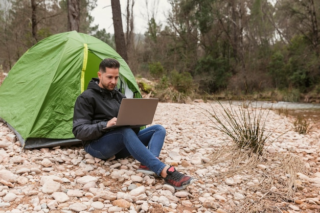 Man beside tent with laptop