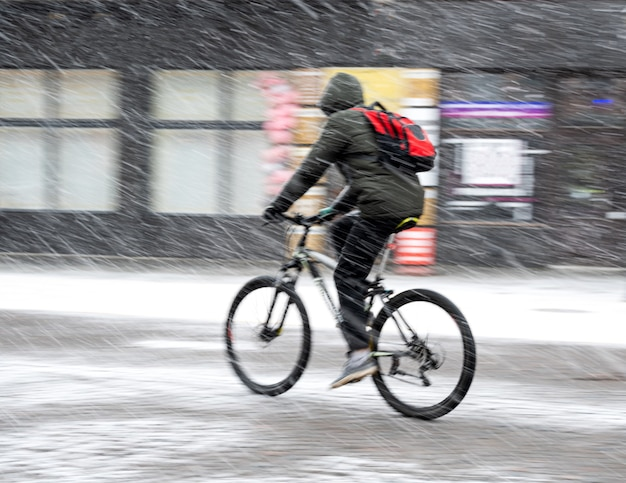 Man on bicycle in the city in snowy winter day.  intentional motion blur. defocused image
