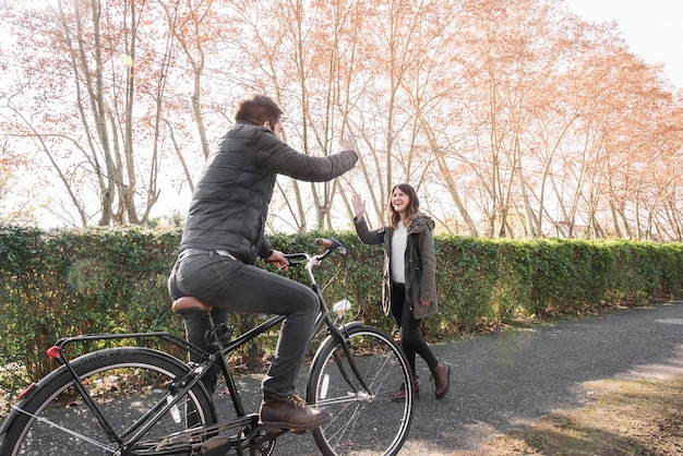 Man on bicycle greeting woman in park