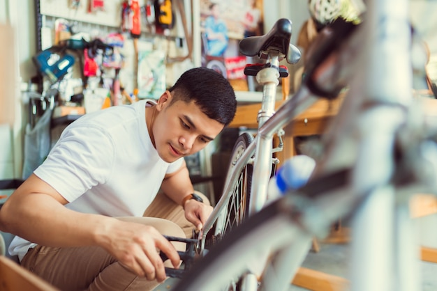 Man bicycle mechanic repairing bicycles
