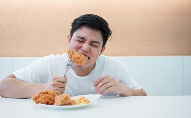 남자는 식당 바에서 식사 닭 튀김 식사를 물고,