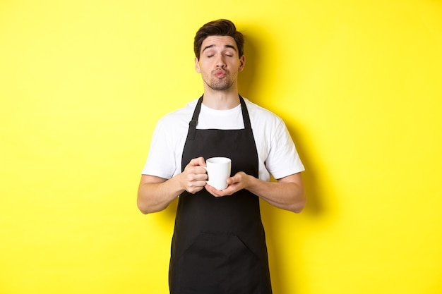 Man in black apron bringing cup of coffee and waiting for kiss, standing over yellow background.