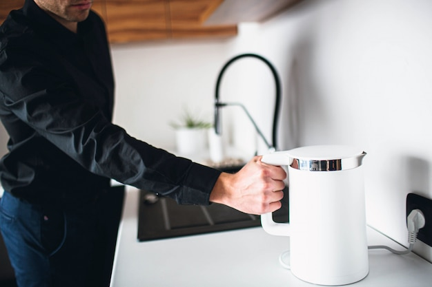 Man in black clothes hold electric kettle in hand