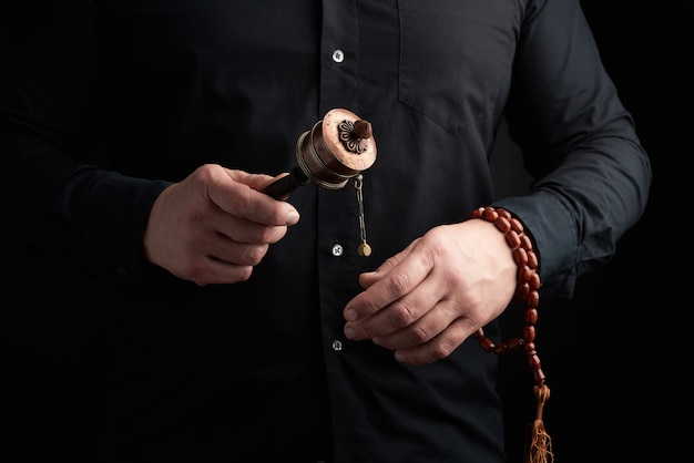 Man in black clothes holds a bronze prayer drum on a wooden handle