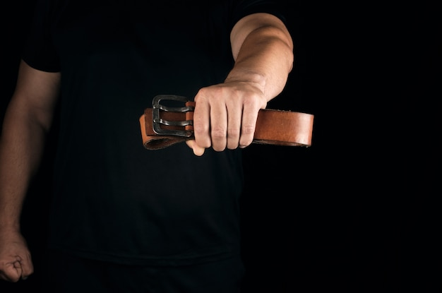 Man in black clothes is holding a brown leather belt with a buckle