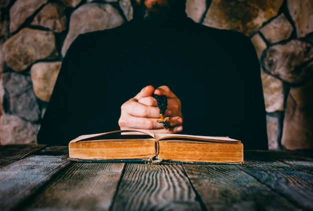 A man in black clothes with a prayer beads in hand praying in front of an old open book.