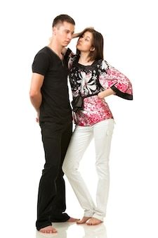 Man in black clothes and woman in multi-colored blouse posing in funny pose and looking at each other
