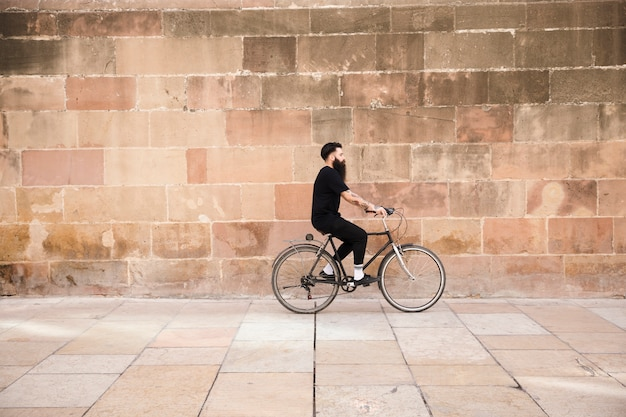 A man in black clothing riding the bicycle in front of wall