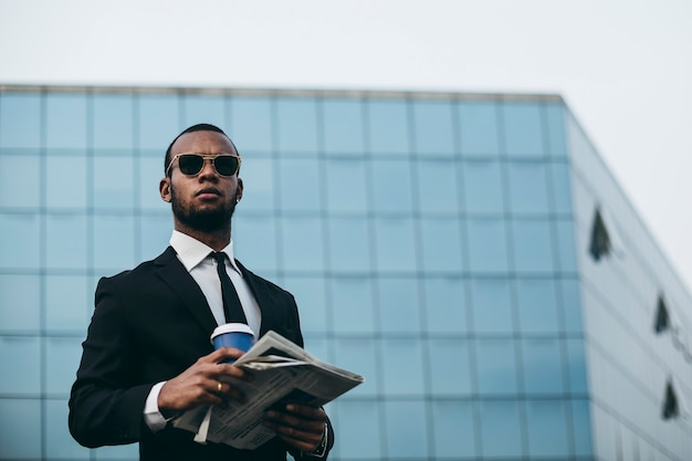 A man of black complexion with sunglasses, he reads the newspaper in front of the building of mirrors. businessman on hiatus