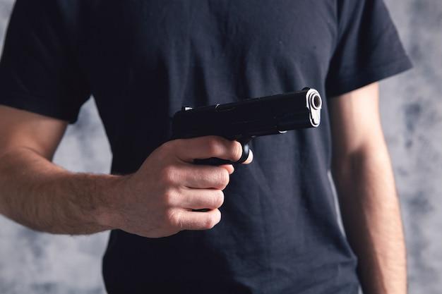 A man in black holds a pistol. firearms