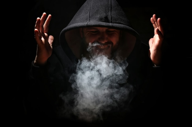 Man in a black hood and smoke on a black background