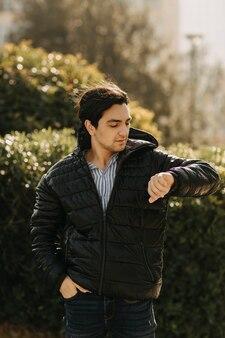 Uomo in giacca nera in piedi nel parco e controllando il suo tempo. foto di alta qualità