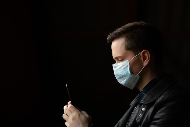 Man in black jacket with face mask using a mobile phone.